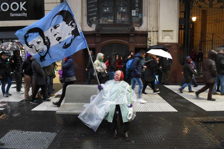 Die Fahne der Demonstrantin zeigt Juan Perón und seine Frau Eva