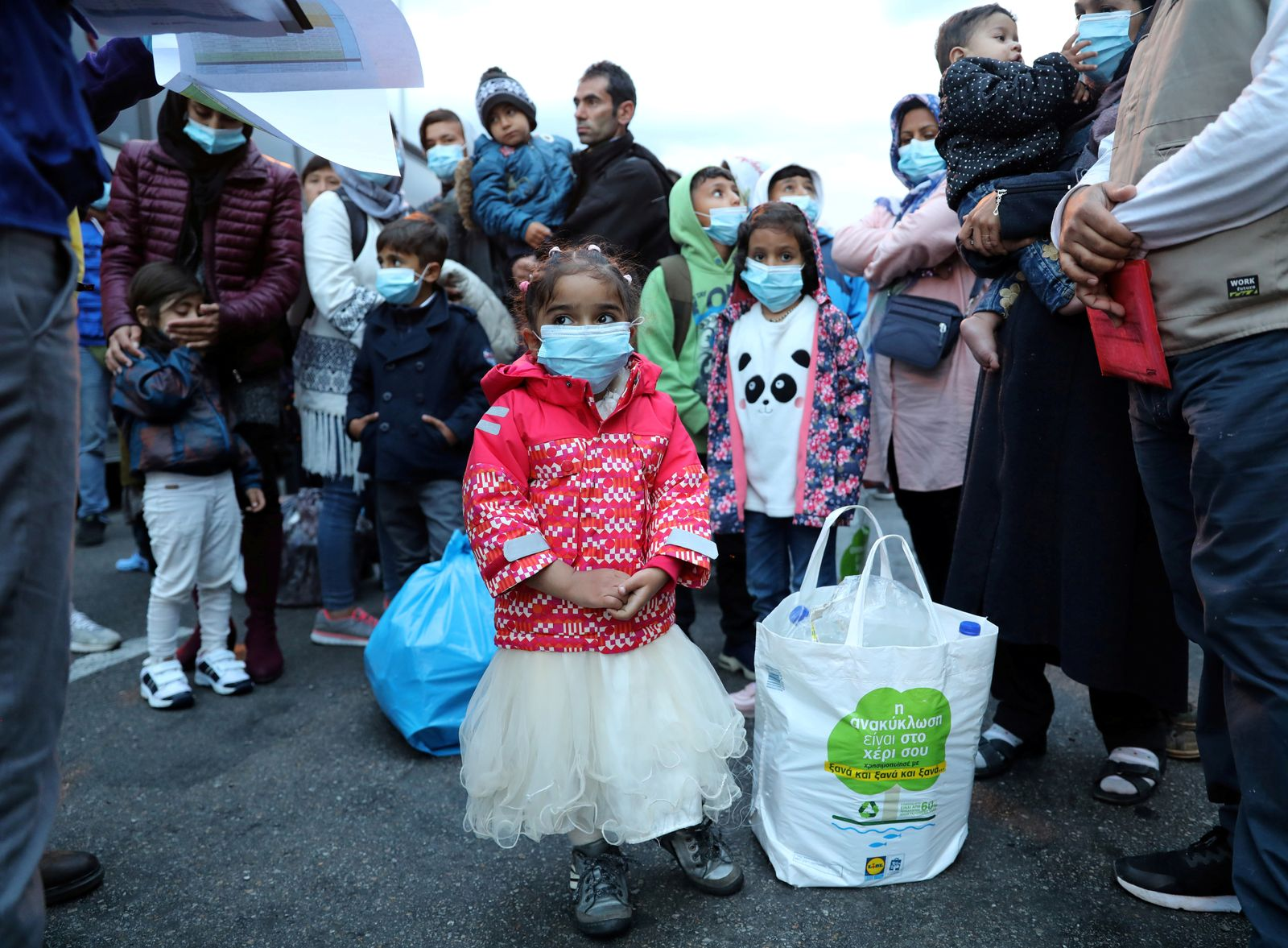 FILE PHOTO: Migrants from the Moria camp in Lesbos wait to board busses at Piraeus port in Athens following the coronavirus disease (COVID-19) outbreak
