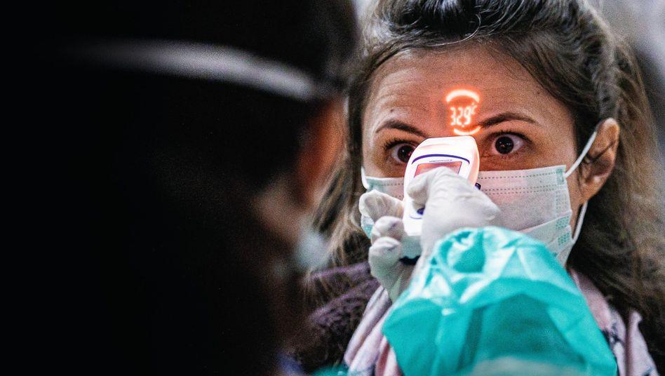 Fiebermessung bei aus Italien einreisender Passagierin am Flughafen im ungarischen Debrecen