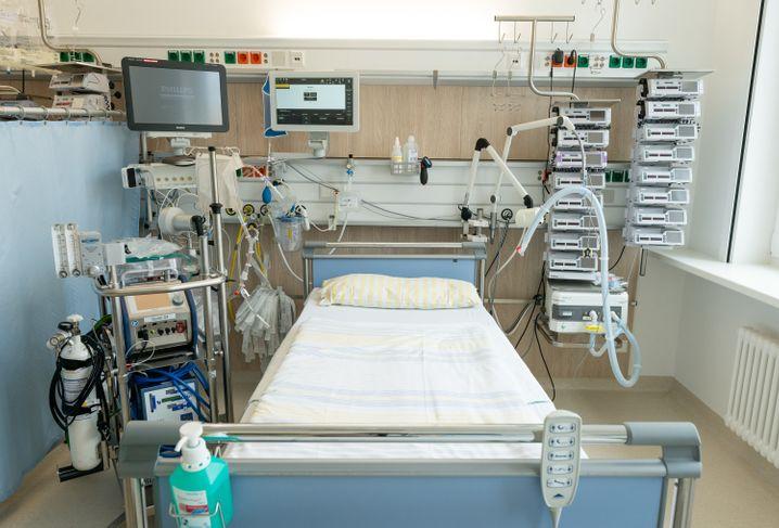 Intensivbett auf einer Station der Uniklinik Dresden: Links neben dem Bett steht eine Herz-Lungen-Maschine, oben befinden sich die Überwachungsmonitore, rechts neben dem Bett stehen ein Beatmungsgerät und Infusionstechnik