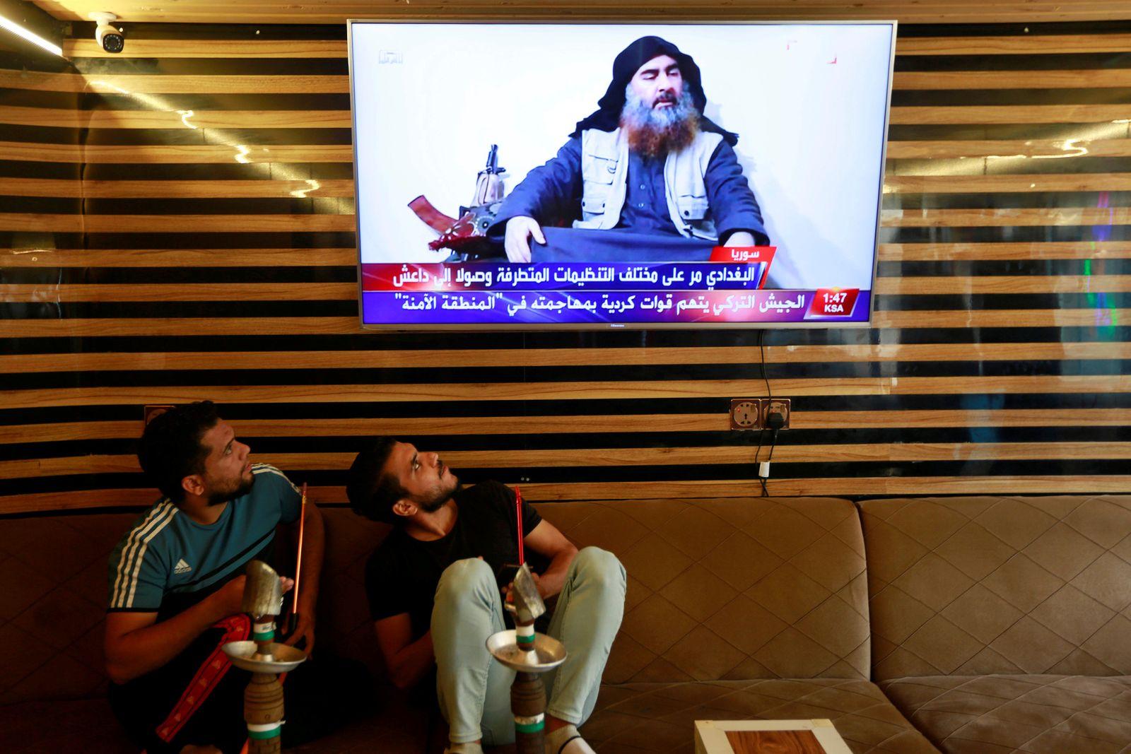 Iraqi youth watch the news of Islamic State leader Abu Bakr al-Baghdadi death, in Najaf