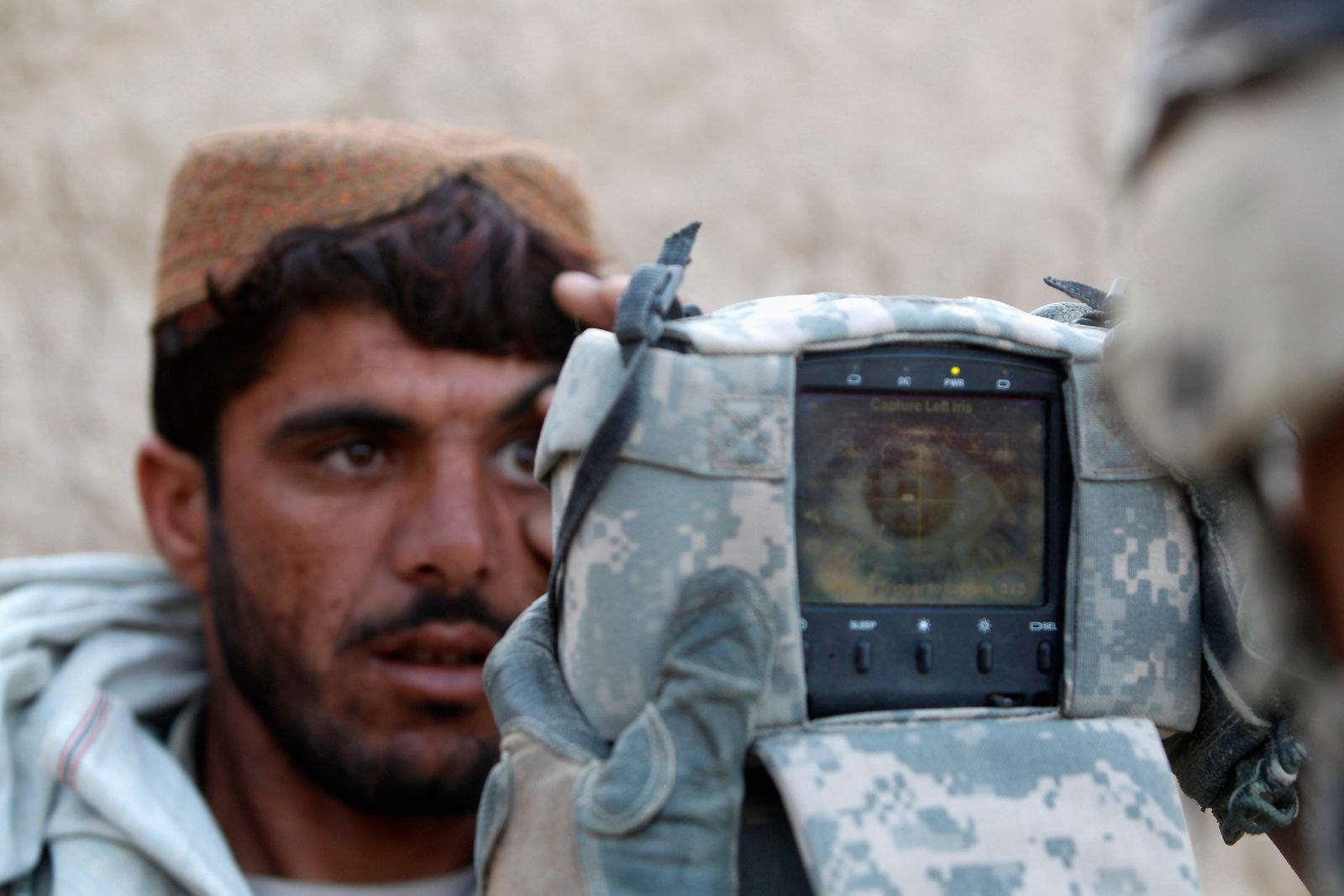 A U.S. Army soldier from 4-73 Cavalry Regiment, 82nd Airborne Division carries out an identification check on an Afghan man with a biometric device during a mission in Zhary district of Kandahar province
