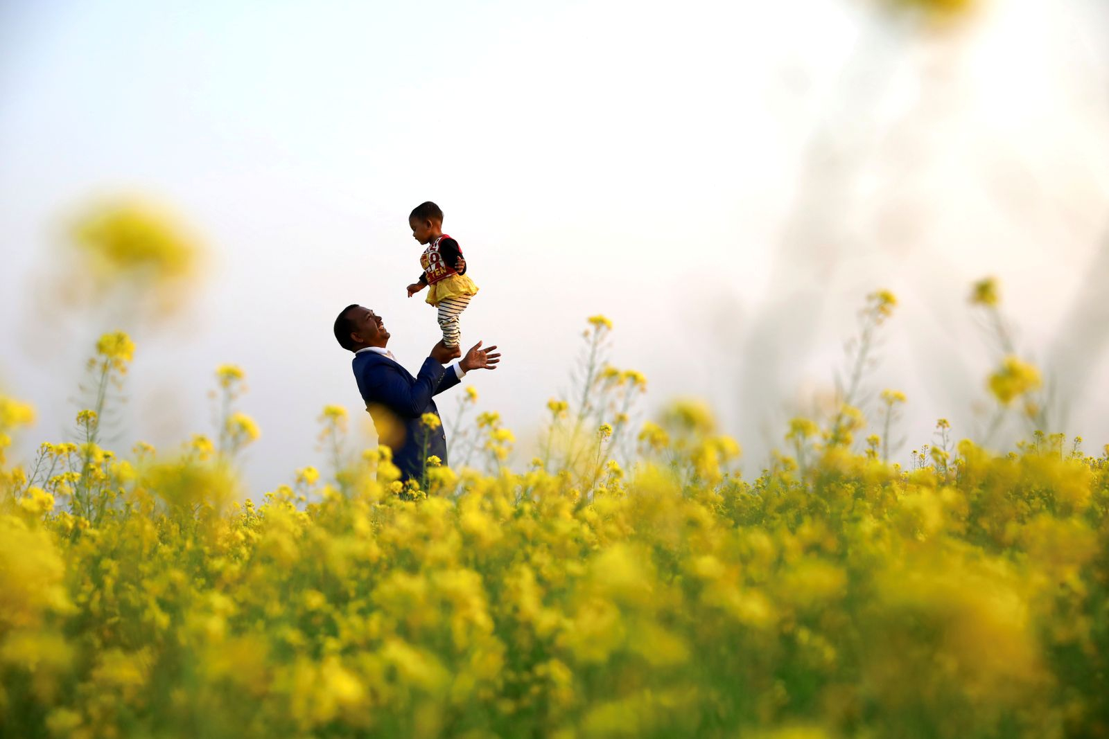 A man holds his daughter on the palm of his hand in a mustard field in Munshiganj
