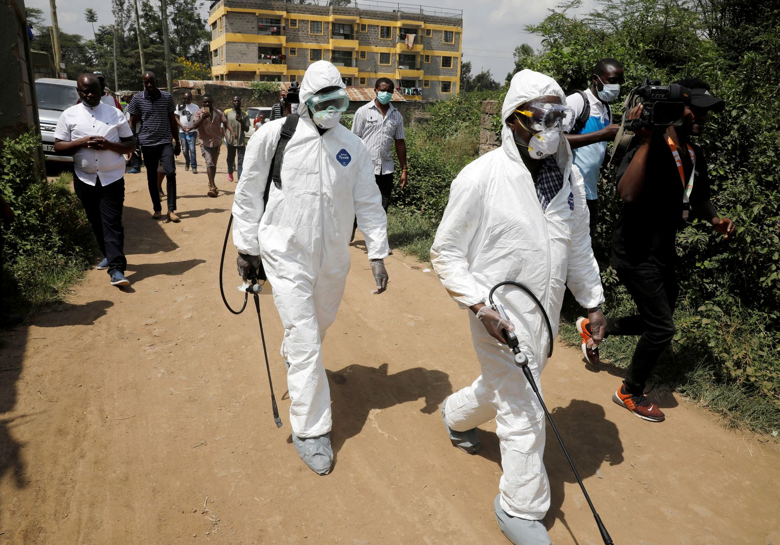 FILE PHOTO: Kenyan health workers dressed in protective suits walk after disinfecting the residence where Kenya's first confirmed coronavirus patient was staying, in the town of Rongai