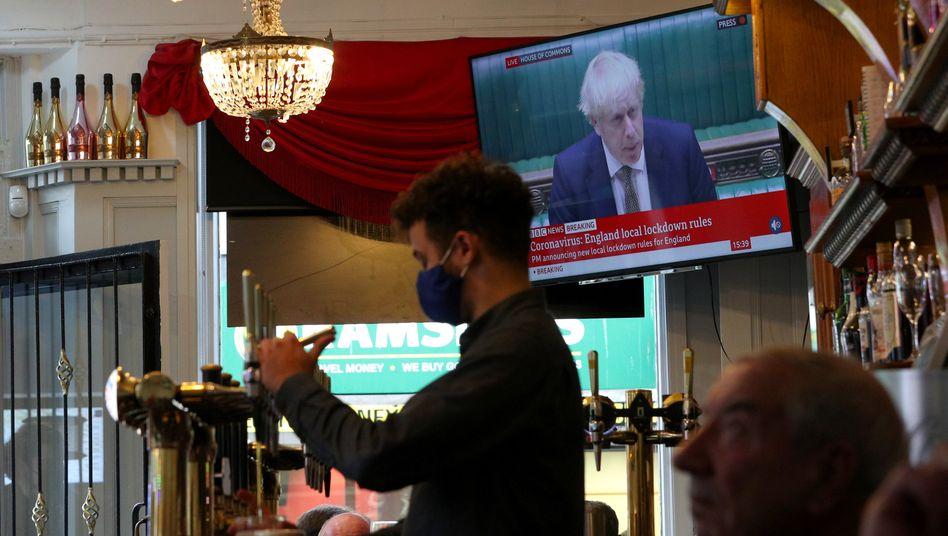 Ein Pub in Liverpool: Im Hintergrund läuft eine Nachrichtensendung aus dem britischen Parlament