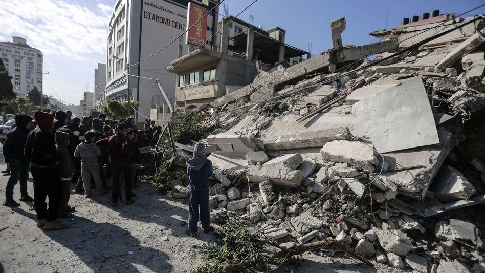 Palästinenser in Gaza stehen vor einem zerstörten Gebäude