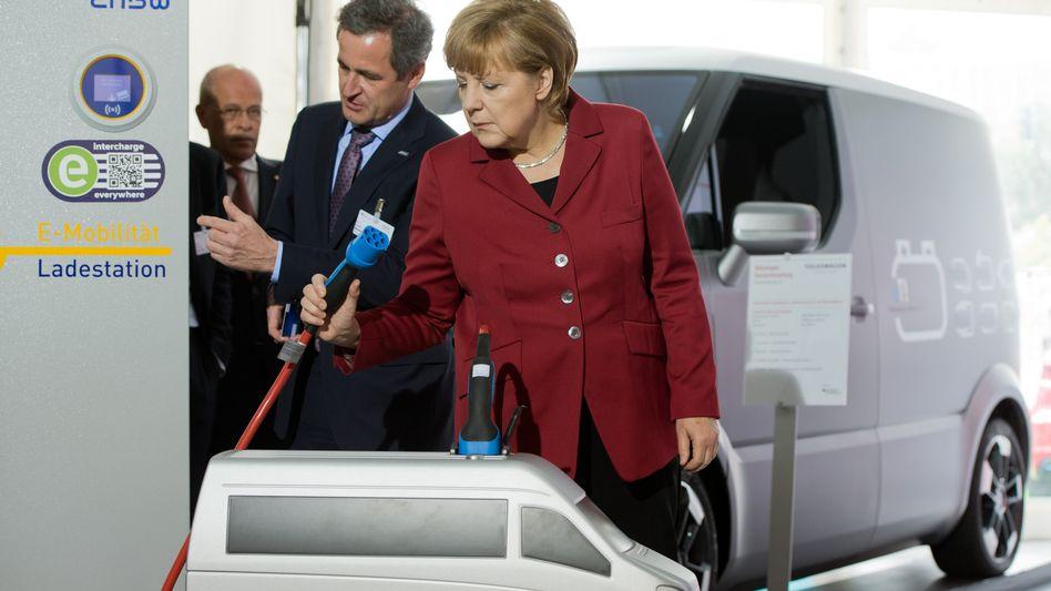 Bundeskanzlerin Merkel vor einer E-Mobil-Ladestation: Stillstand beim Mobilitätswandel