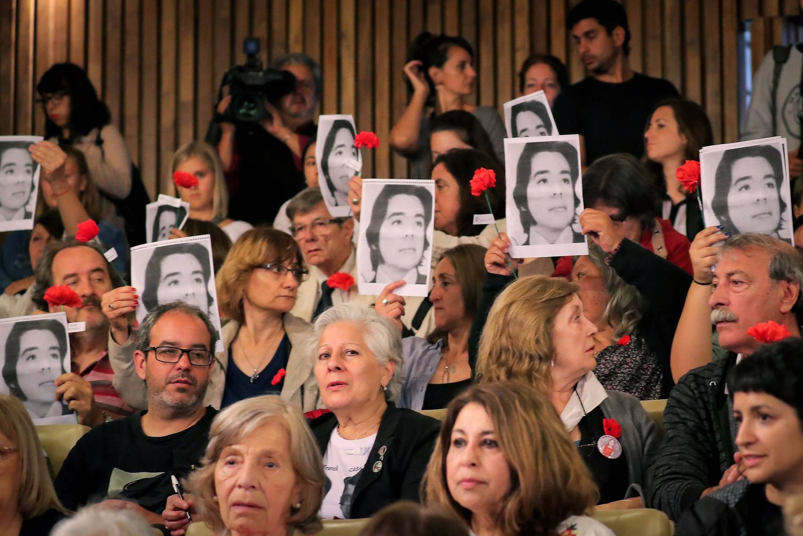 Relatives of the victims show photos and flowers during the oral trial for crimes committed during t