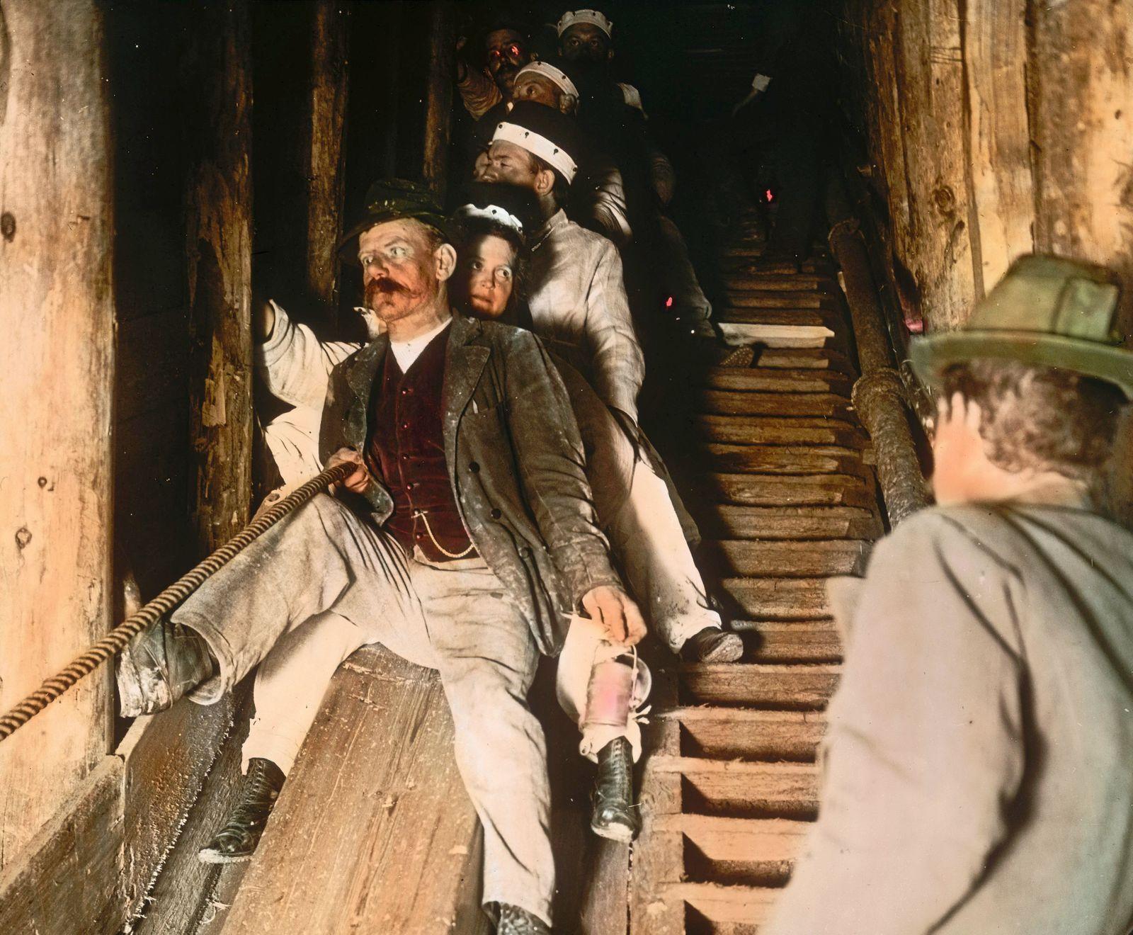 Tour guide and tourists in the salt mine of Hallstatt: departure on the chute. Salzkammergut. Upper Austria. Hand-colored lantern slide. Around 1910.