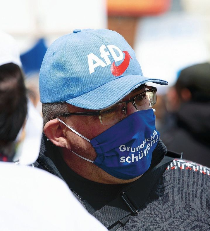 A corona lockdown protester in Munich wears a hat with the logo of the right-wing populist AfD party.