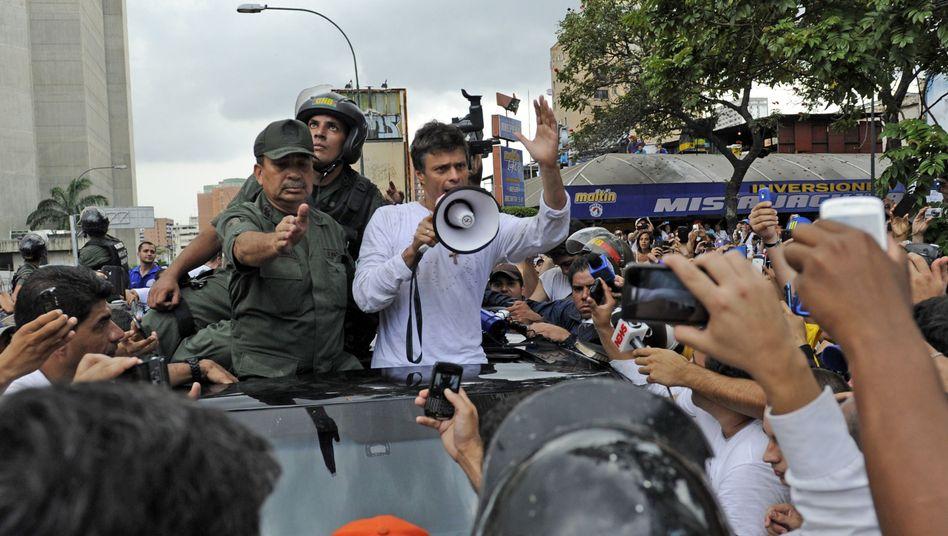 """López beruhigt seine Anhänger während seiner Festnahme per Megafon: """"Lasst uns friedlich auseinandergehen"""""""