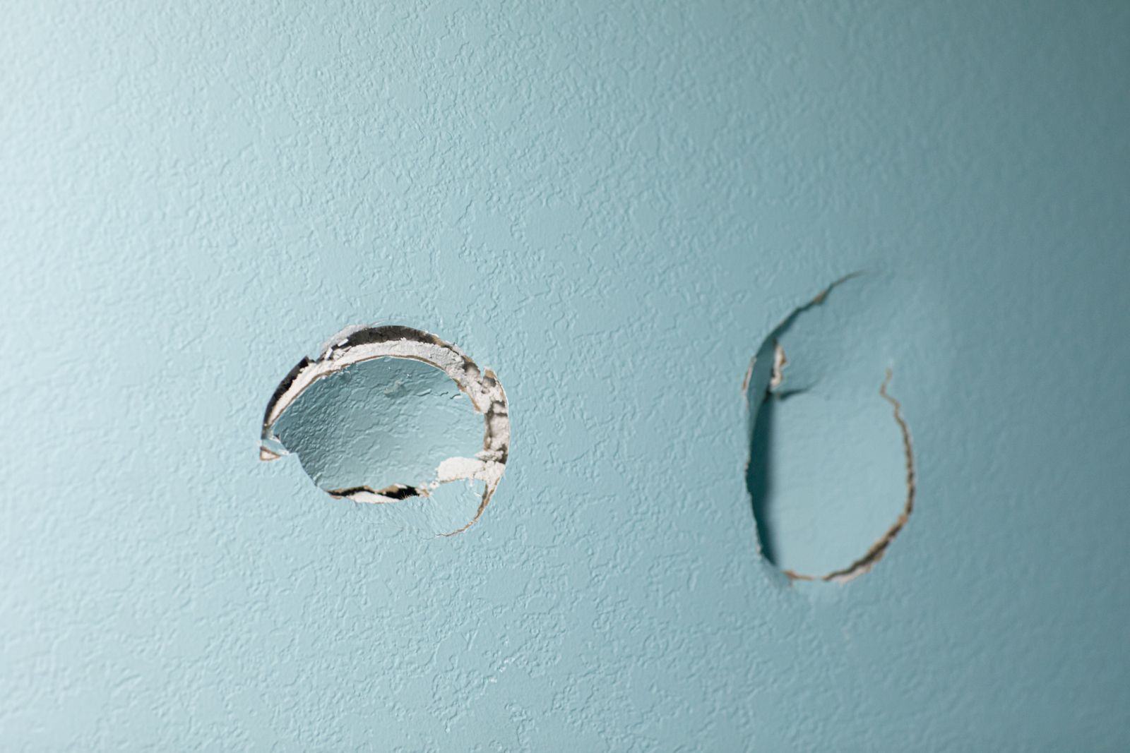 Blue wall in a home with two holes in the sheetrock