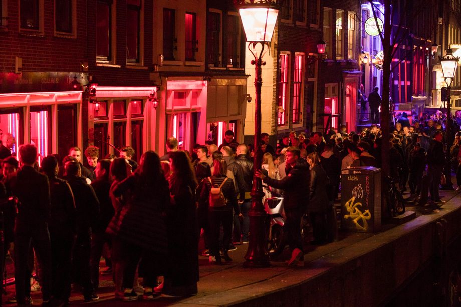 Tourists shuffle, shoulder to shoulder, through Amsterdam's red-light district in this March, 2019 photo.