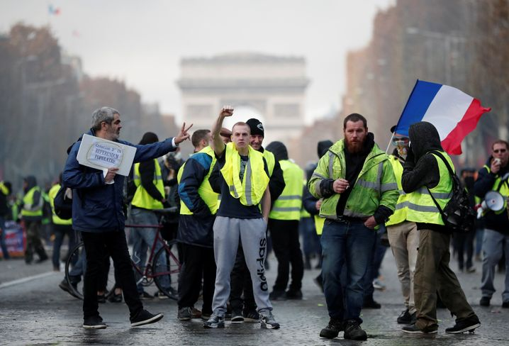 A protester wearing yellow vest, a symbol of a French drivers' protest against higher fuel prices, gestures during riots on the Champs-Elysees in Paris, France, November 24, 2018. REUTERS/Benoit Tessier - RC13E269EED0