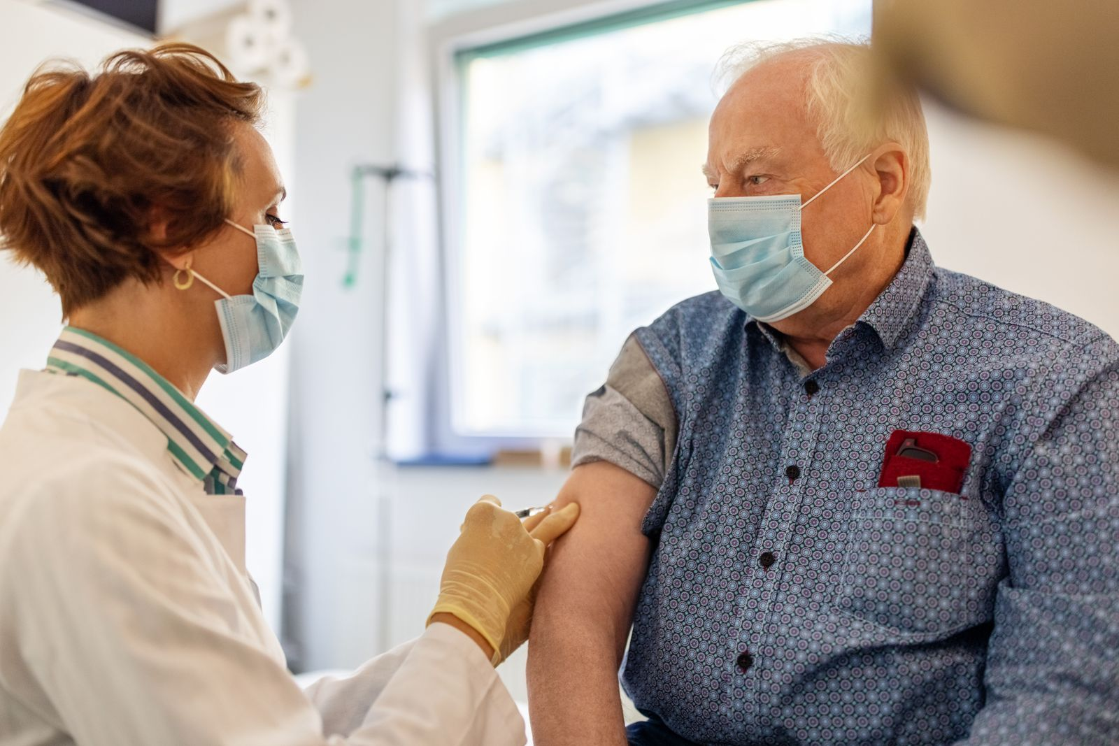 General practitioner giving flu shot to a senior man in clinic