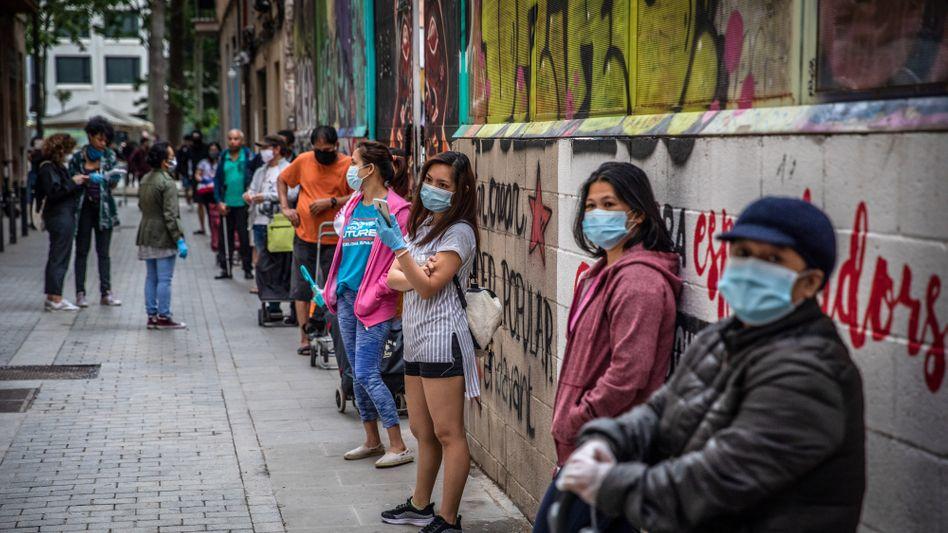 Menschen warten in einer Schlange vor einer kostenlosen Essensausgabe in Barcelona (im Mai 2020)
