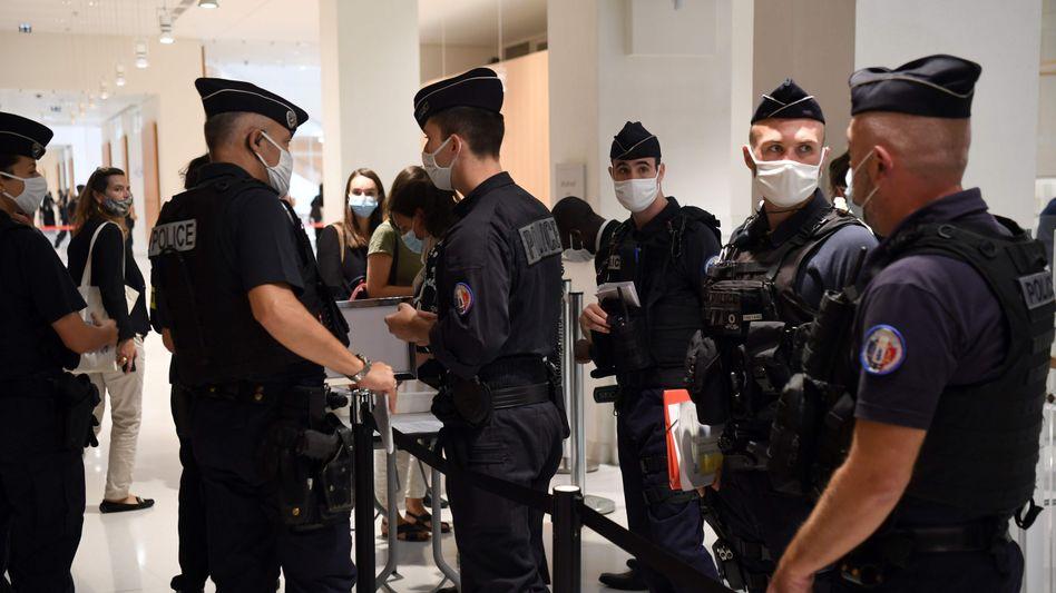 Polizeibeamte kontrollieren Besucher beim Prozessauftakt