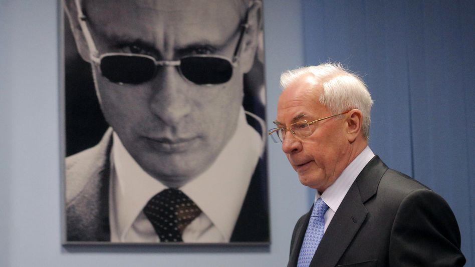 Ukraines früherer Premier Asarow (vor einem Putin-Porträt): Vorwürfe gegen Deutschland und die EU