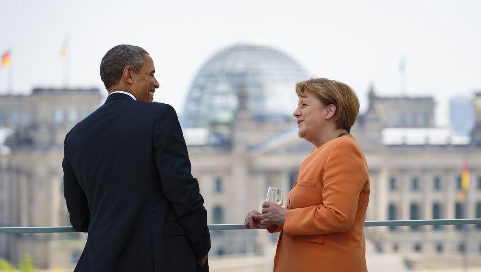 US President Barack Obama and German Chancellor Angela Merkel speak on the terrace of the Chancellery in Berlin.