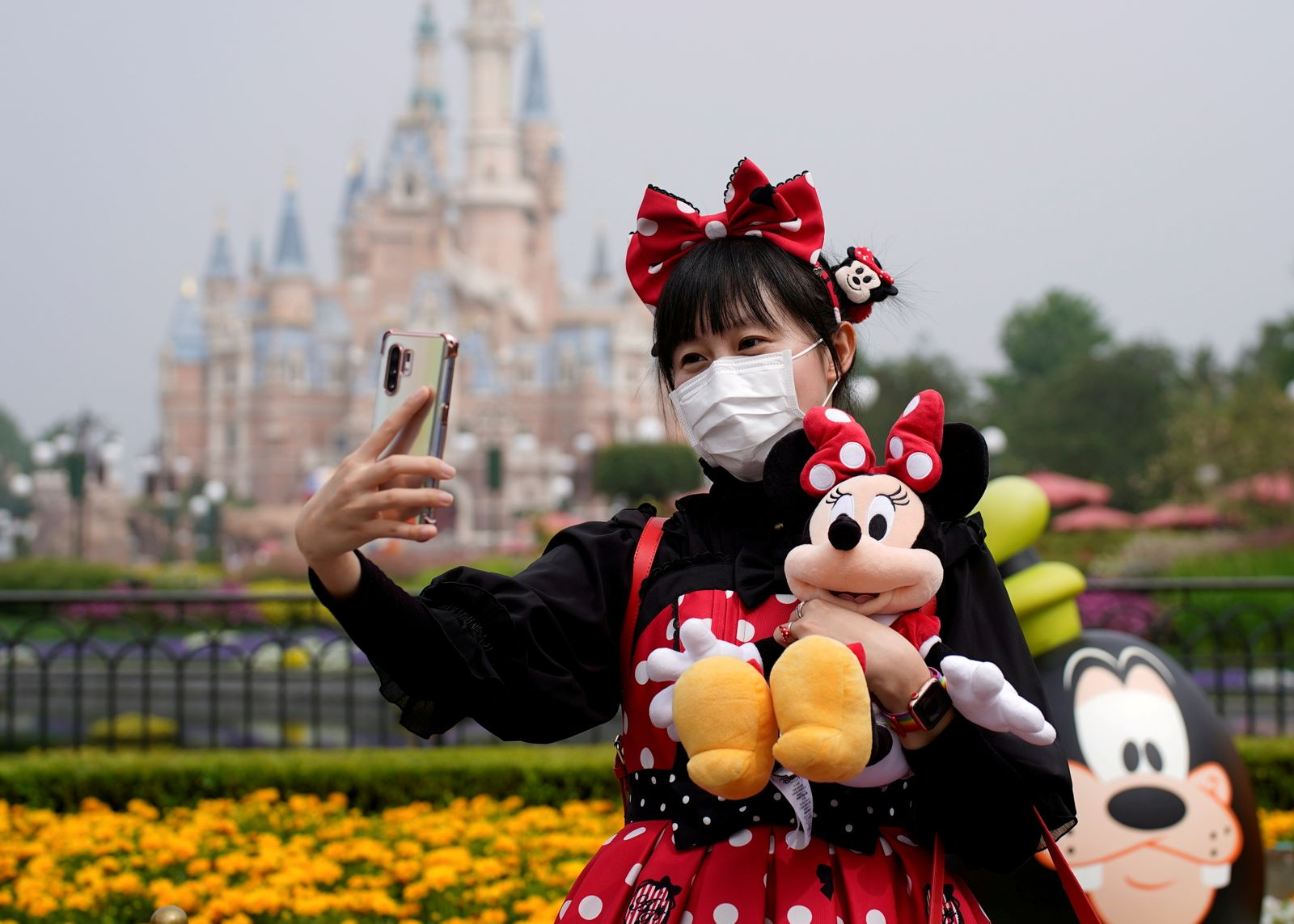 FILE PHOTO: A visitor takes a selfie while wearing a protective face mask at Shanghai Disney Resort as the Shanghai Disneyland theme park reopens following a shutdown due to the coronavirus disease (COVID-19) outbreak, in Shanghai