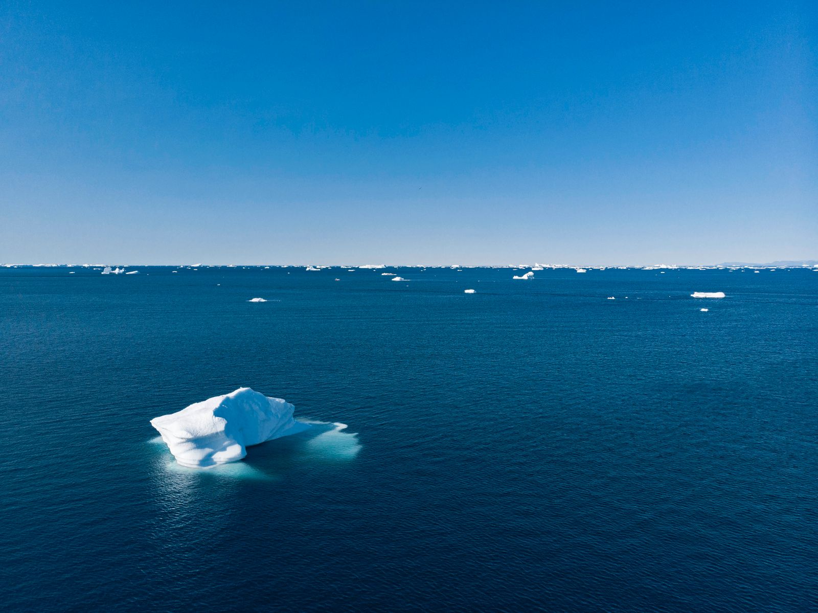 Polar ice melting on vast blue Atlantic Ocean Greenland Polar ice melting on sunny vast blue Atlantic Ocean Greenland. *