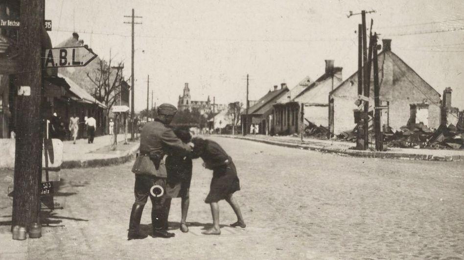 Im privaten Fotoalbum des Polizisten Josef Baur findet sich ein Bild, auf dem er zwei jüdische Mädchen brutal züchtigt (Juli 1941).