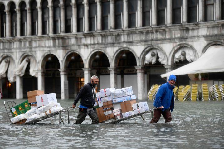 Überschwemmung in Venedig 2019: Männer waten mit Kartons und Lebensmitteln durch das Hochwasser auf einem überfluteten Platz