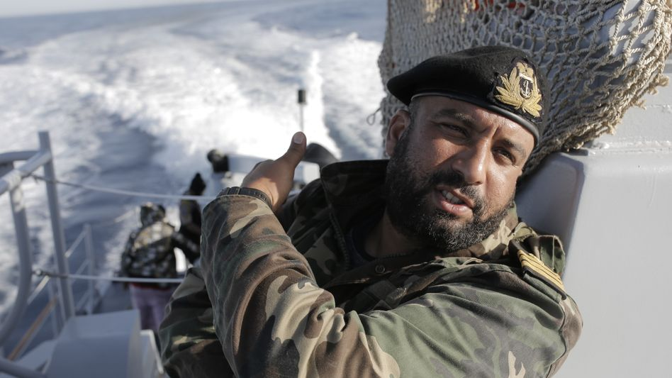 A Libyan coast guard officer on board the Fezzan: Hauling refugees back to prison camps