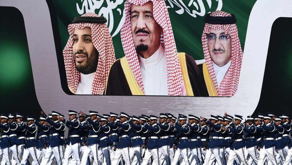 Newly graduated Saudi air force officers march in front of a banner bearing portraits of King Salman bin Abdulaziz (center), Mohammed bin Nayef (right), and Crown Prince Mohammed bin Salman.