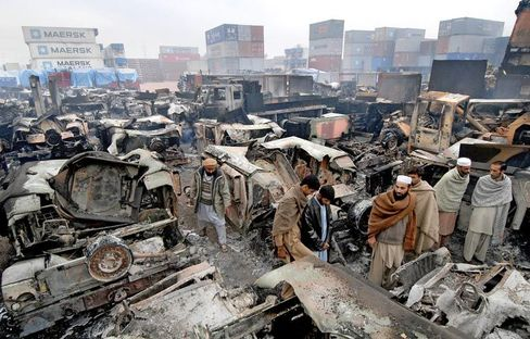 Pakistani employees inspect burned-out trucks at a NATO terminal outside the northwestern city of Peshawar.