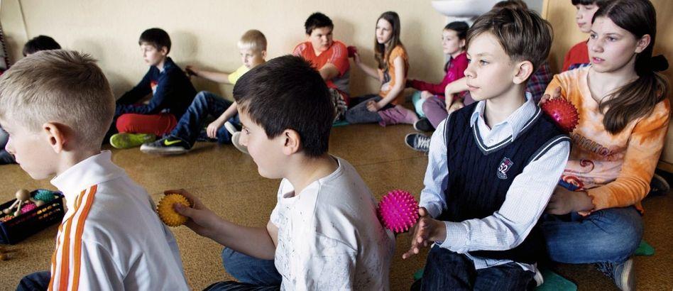 Grundschüler in Berlin-Hellersdorf: Die Bewegungen erfolgen beiläufig, während die Kinder zuhören und Zwischenfragen stellen