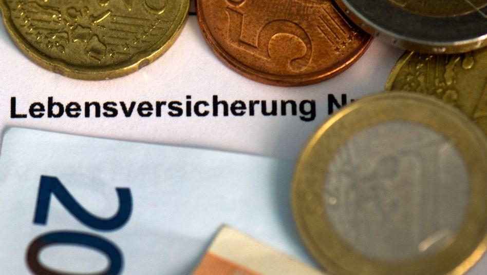 Versicherungsschein mit Münzen: Lebensversicherung weniger rentabel