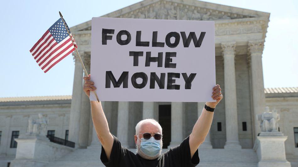 """Follow the money"" - folgt dem Geld, Trumps Geld: Demonstrant vor dem Supreme Court in Washington"