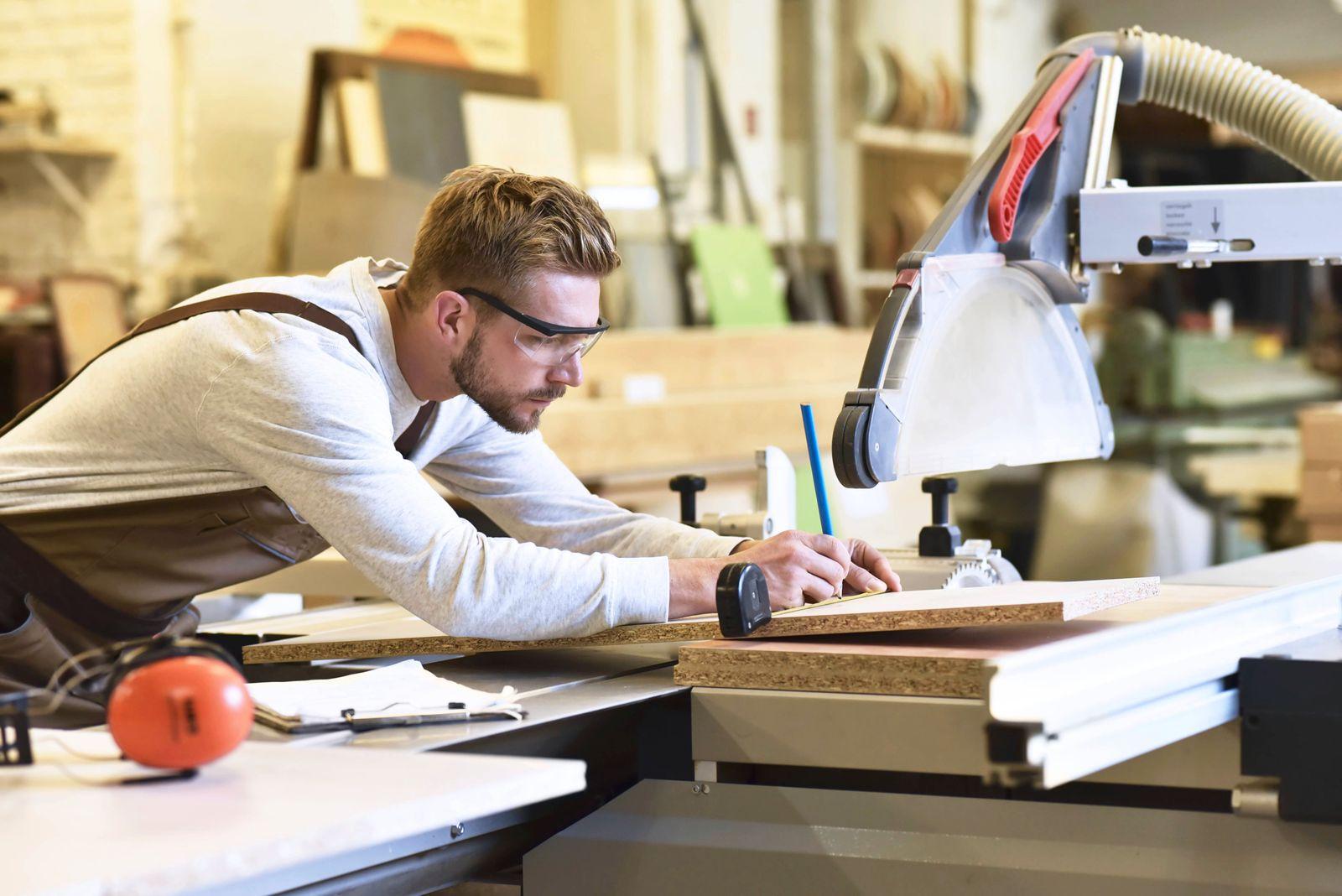 Carpenter measuring wooden boards in his workshop model released Symbolfoto property released PUBLIC