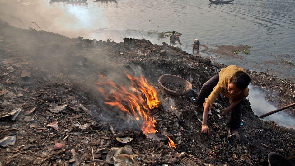 Ein Junge in Bangladesch verbrennt Müll: Armut ist einer der Hauptfaktoren, die weltweit zu Bleivergiftungen von Kindern führen