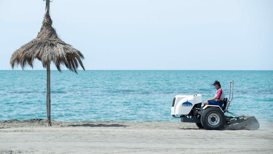 Ein Mann bereitet in der Nähe von Rom einen Strand auf die Wiederöffnung im Sommer vor