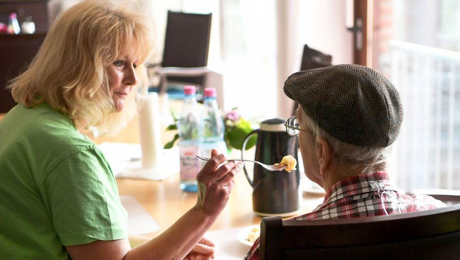 Eine Pflegerin betreut einen alten Mann