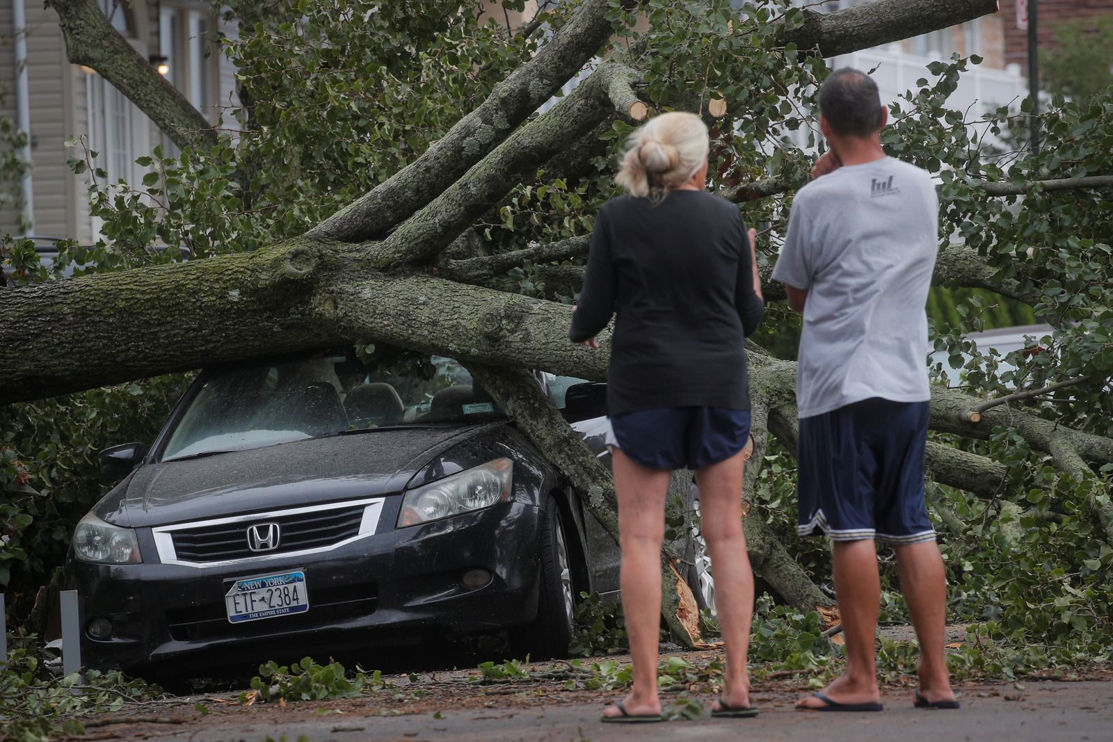People look at a fallen tree on a car in the aftermath of Tropical Storm Isaias in the Rockaway area of Queens in New York