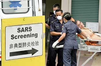 Pfleger tragen einen infizierten Mann in ein Krankenhaus in Singapur