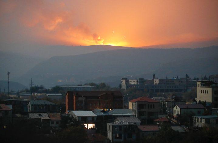 Hinter einem Berg steigen Flammen auf, vorn liegt die Stadt Stepanakert