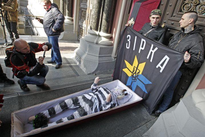 Mitglieder des Regiments Asow, eines paramilitärischen Freiwilligenbataillons, stehen am 01.03.2017 zusammen mit einem Sarg und dem Konterfei Gontarjewas vor der Nationalbank in Kiew