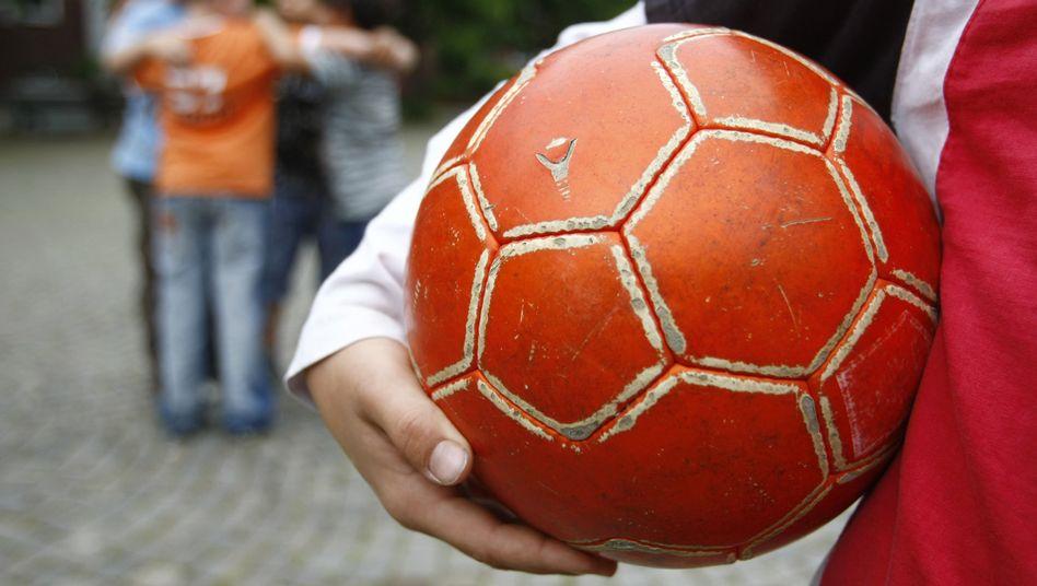 Ein Junge hält einen Fußball (Symbolbild)