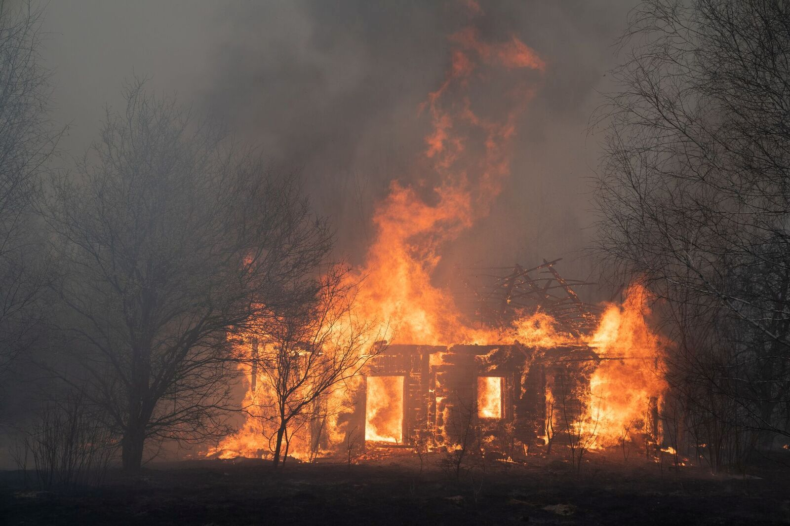 A view shows a wooden house on fire in Lyudvynivka in Kiev Region