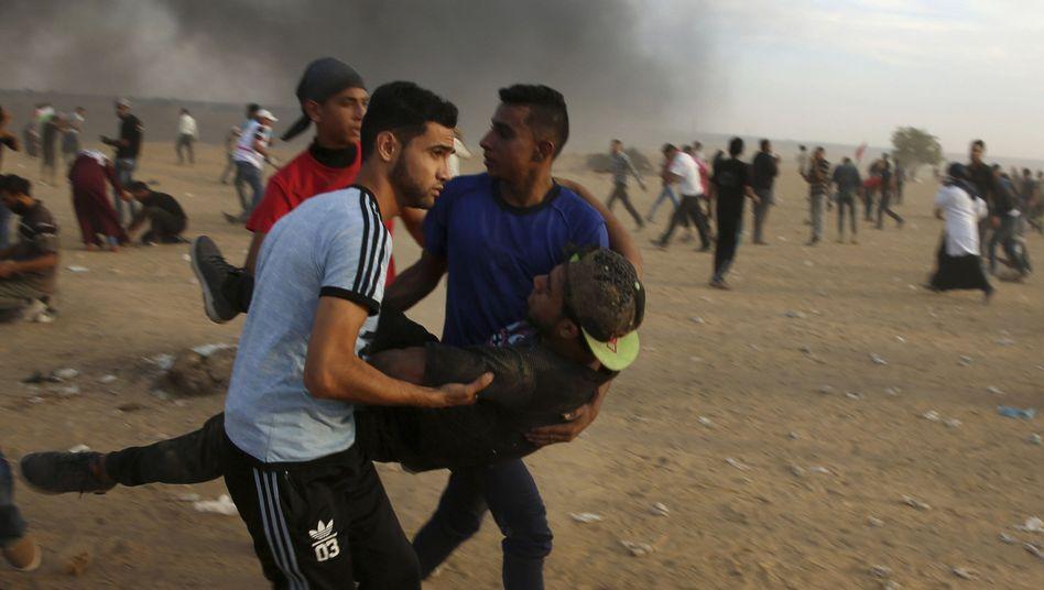 Protestierende tragen einen Verletzten am Gazastreifen