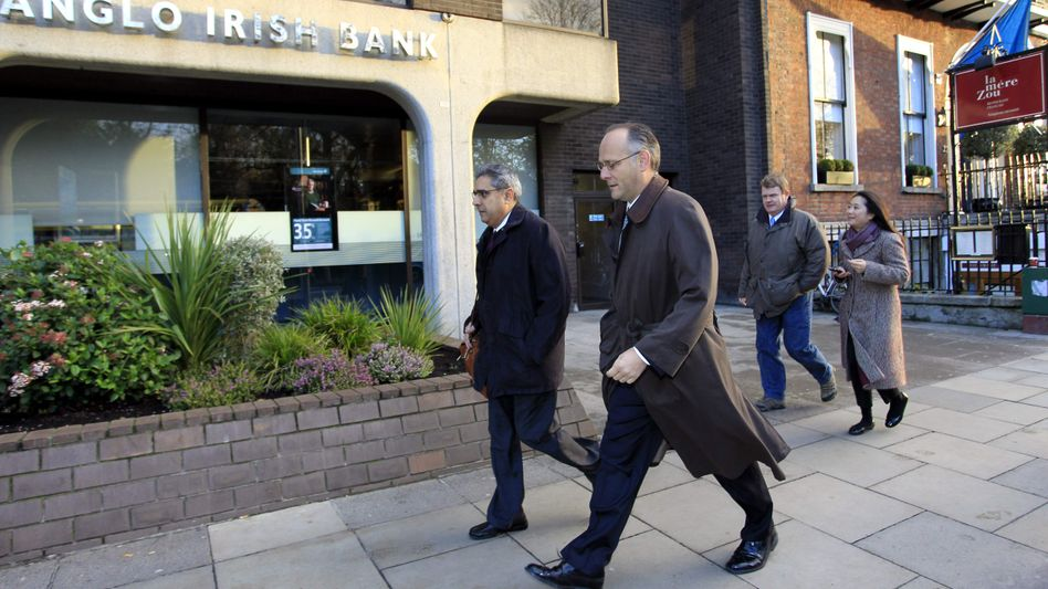 Ajai Chopra, of the IMF, and colleagues pass one of Ireland ailing banks, Anglo Irish, in Dublin on Thursday.