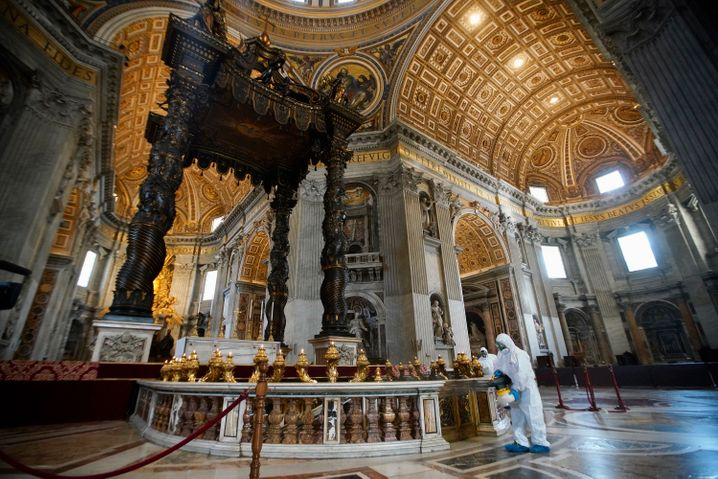 Arbeiter in Schutzkleidung desinfizieren den Petersdom