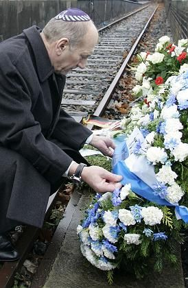 Israeli Prime Minister Ehud Olmert lays a wreath Tuesday at a Berlin train station used for Holocaust deportations.