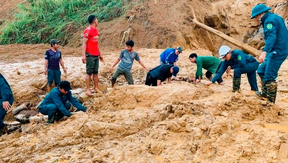 Dorfbewohner und Soldaten graben sich nach einem Erdrutsch in der Provinz Quang Nam durch den Schlamm