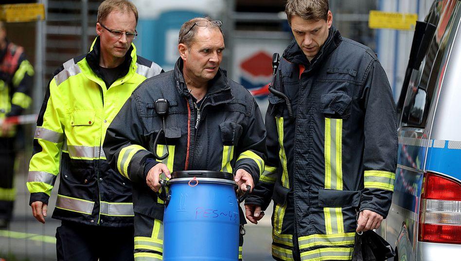 Ein Feuerwehrmannträgt eine Tonne aus dem Wohnkomplex in Köln, in dem der Mann lebte (Archiv)