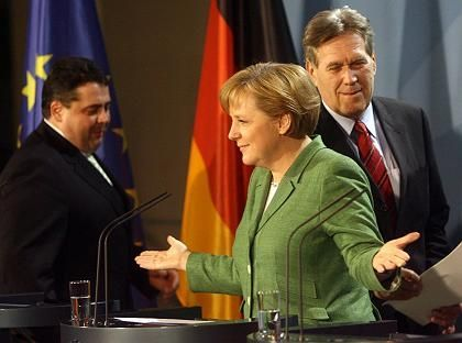 Chancellor Angela Merkel talks to the press after Monday's energy summit, with Economy Minister Michael Glos (right) andEnvironment MinisterSigmar Gabriel by her side.